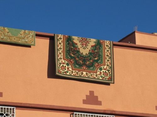 A rug hanging over the edge of a building in Tinghir